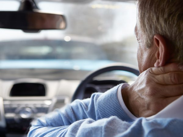 man holding neck in a car used for blog post on How to Treat Whiplash after a Car Accident