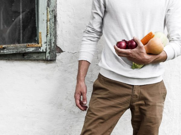 man holding fruit and veggies in his hand